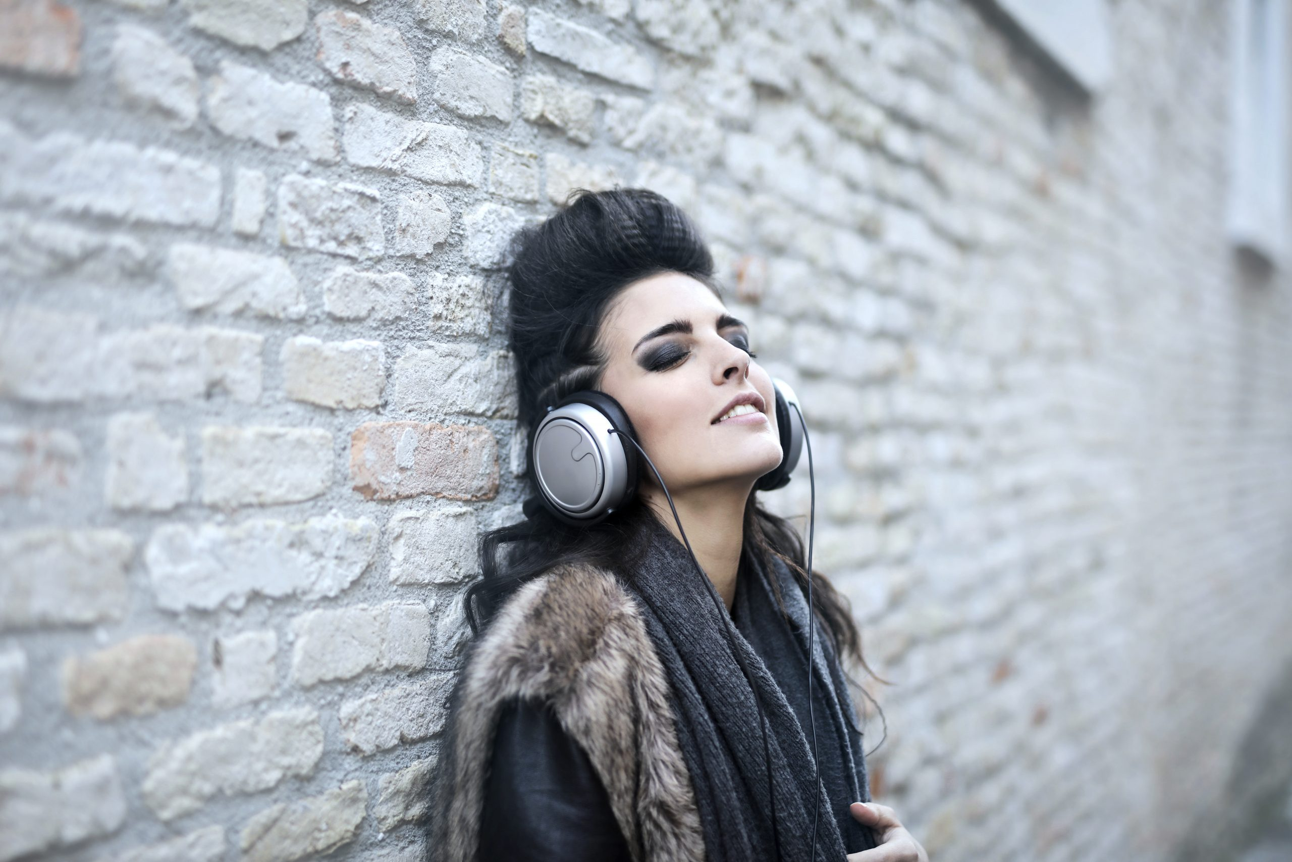 Informal young woman listening to music near grunge wall