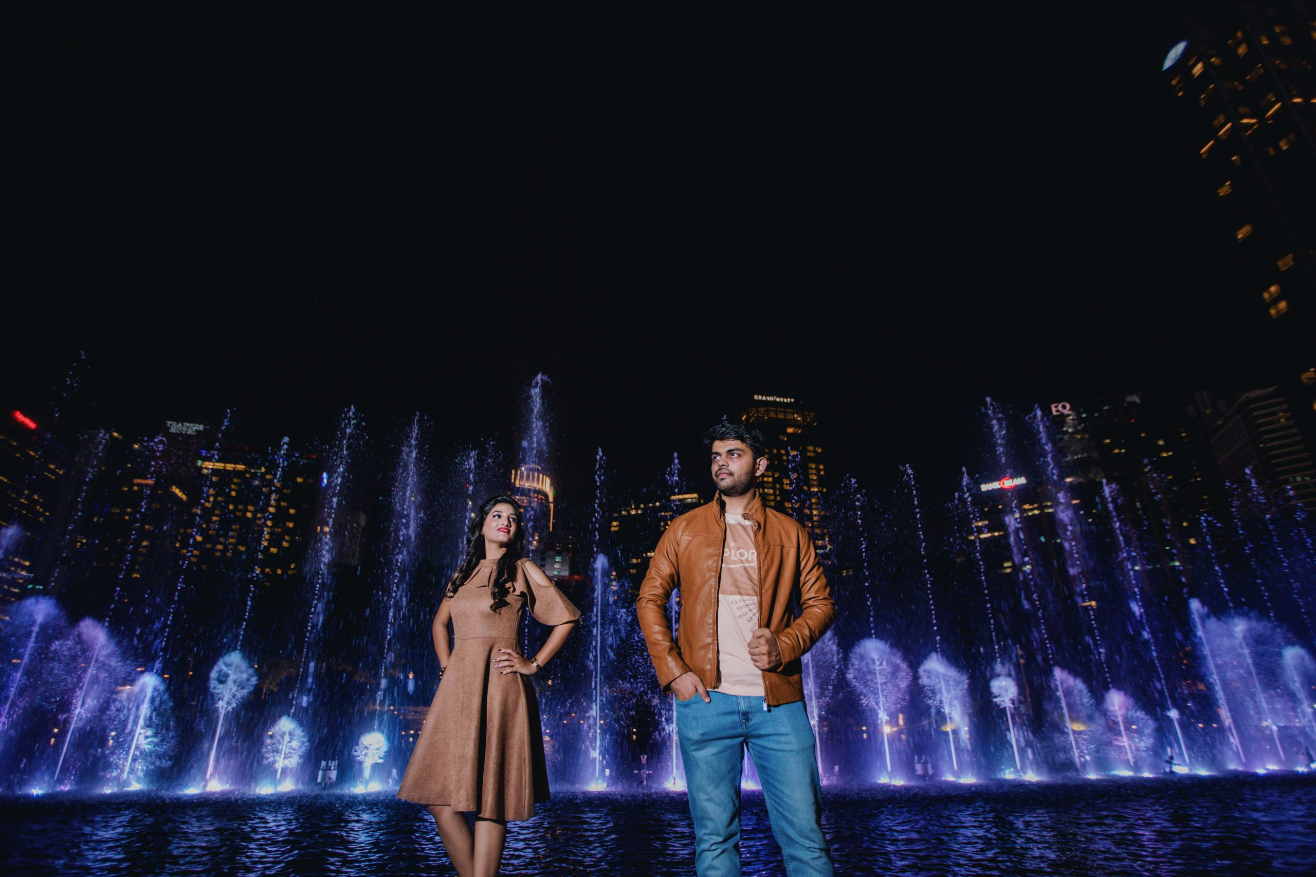 man and woman standing in front of fountain in park