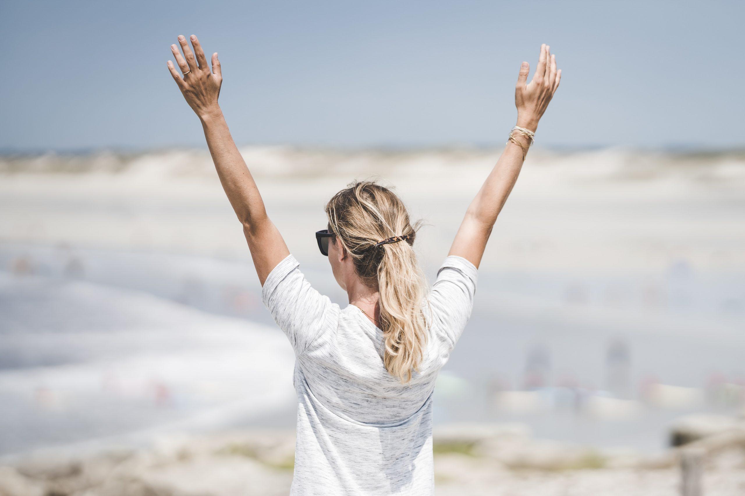 woman in white long sleeve shirt raising her hands