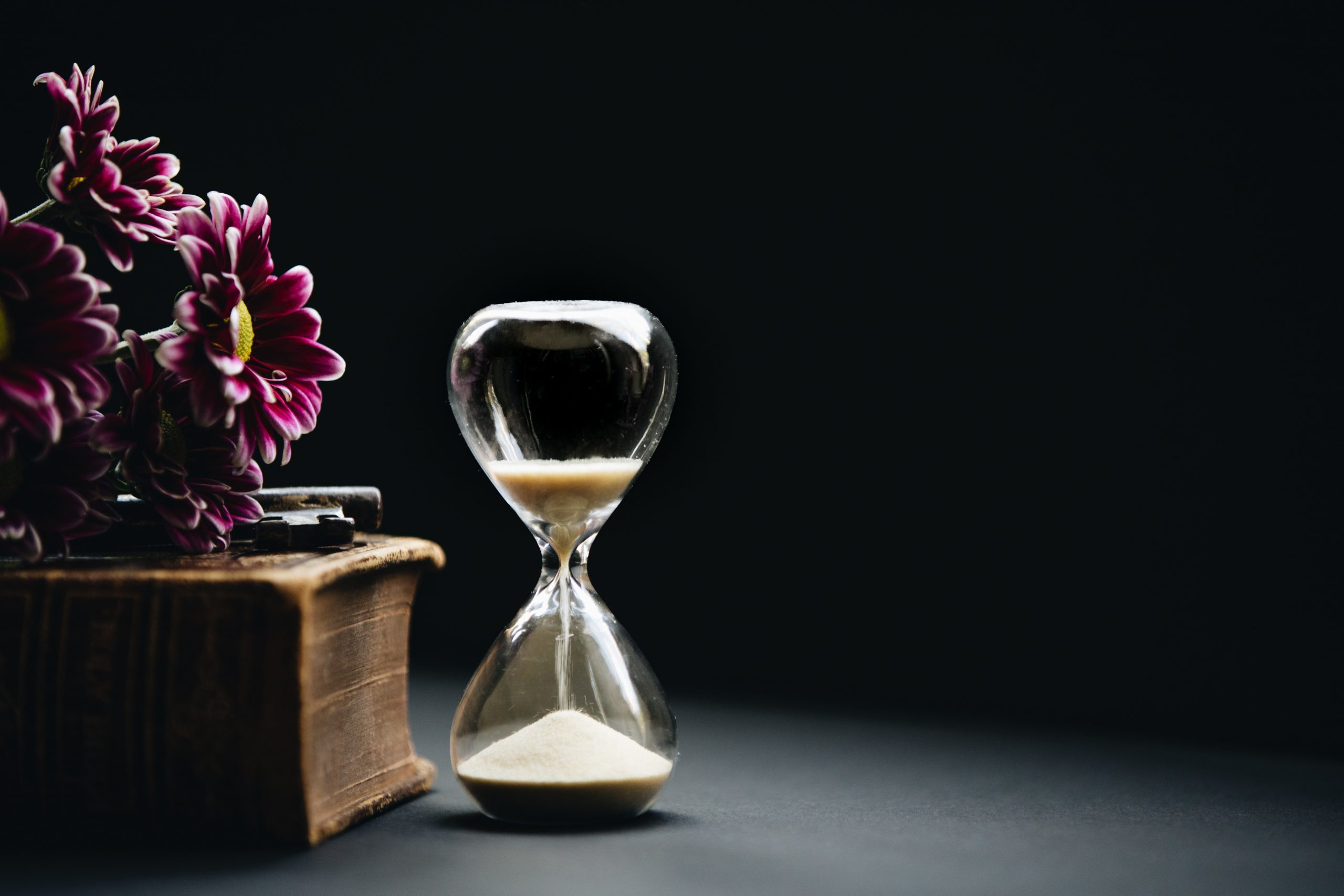 clear hour glass beside pink flowers