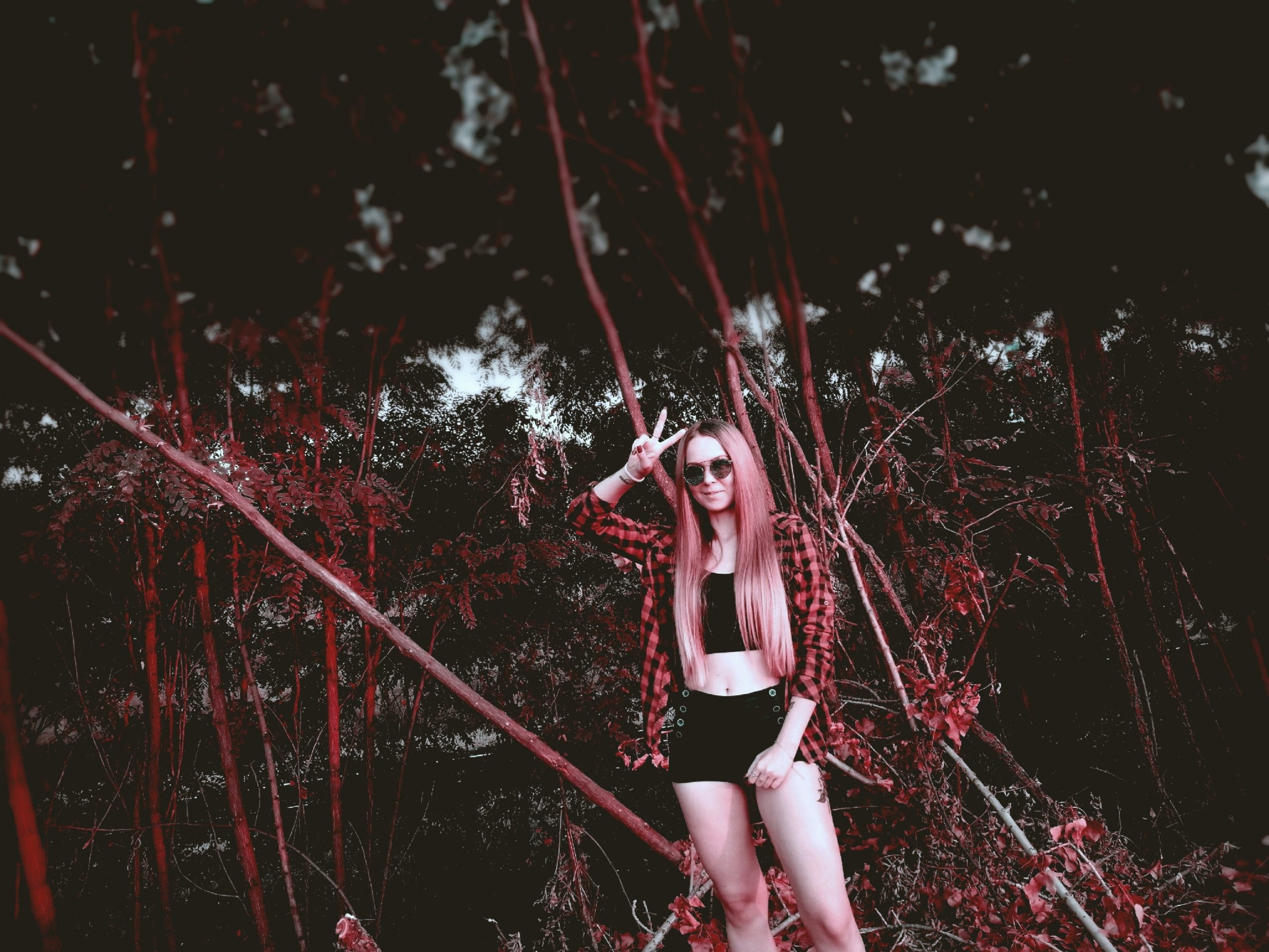 woman in black and white striped tank top and black shorts standing on forest