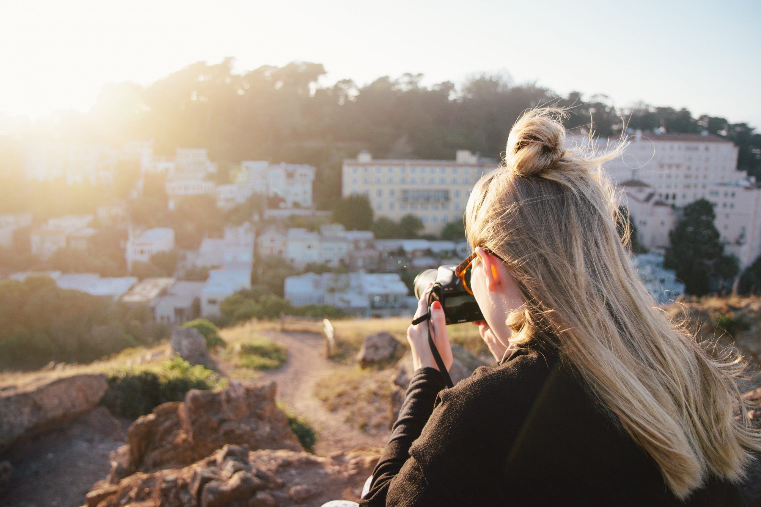 woman in black coat taking photo of city during daytime
