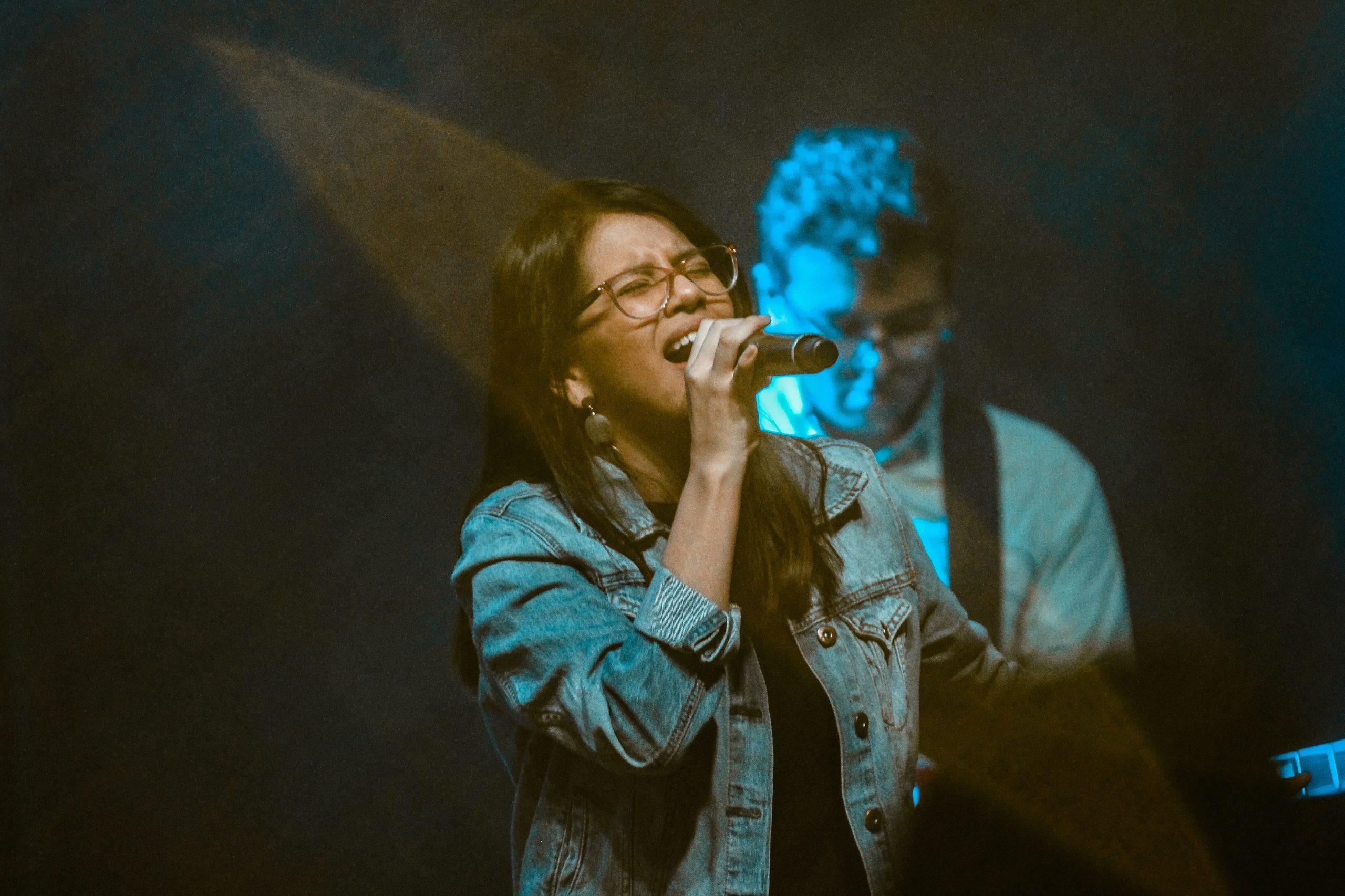 woman wearing blue denim jacket singing near man playing guitar