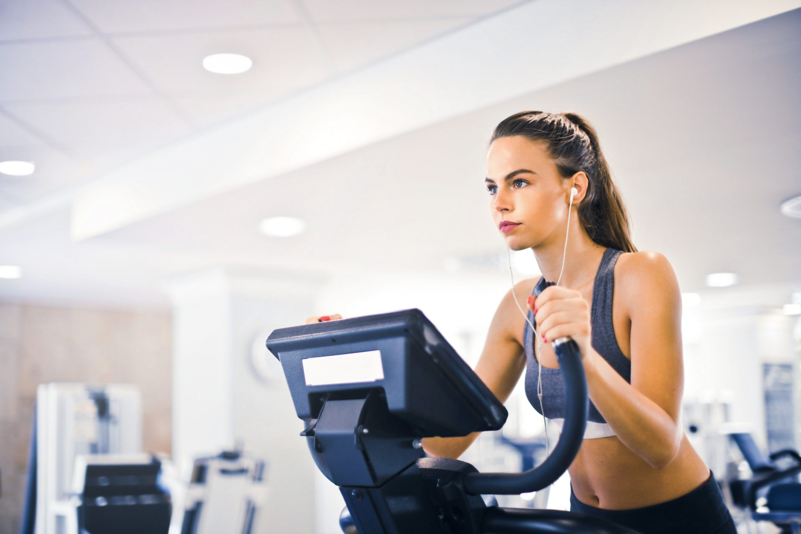 Young female athlete training alone on treadmill in modern gym